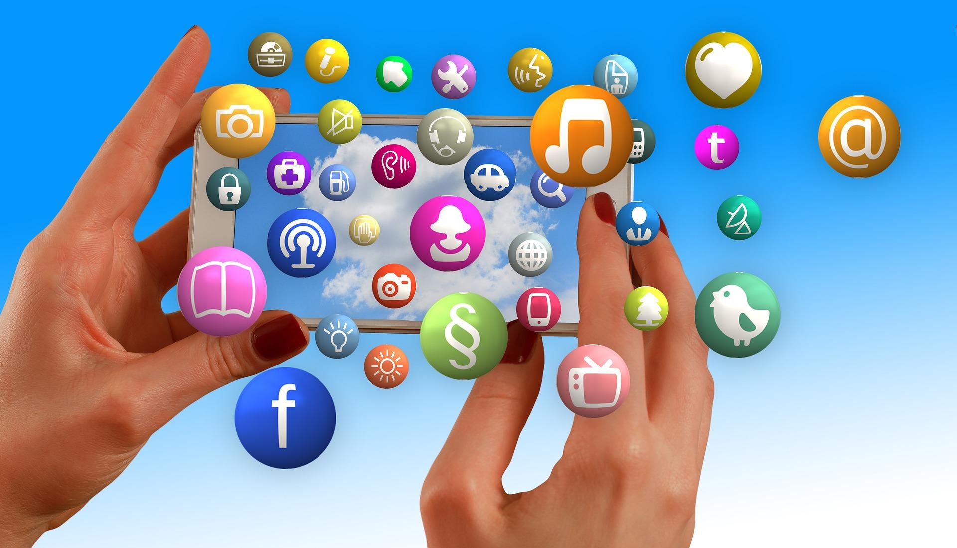 Hender som holder en smarttelefon med ikoner fra sosiale medier