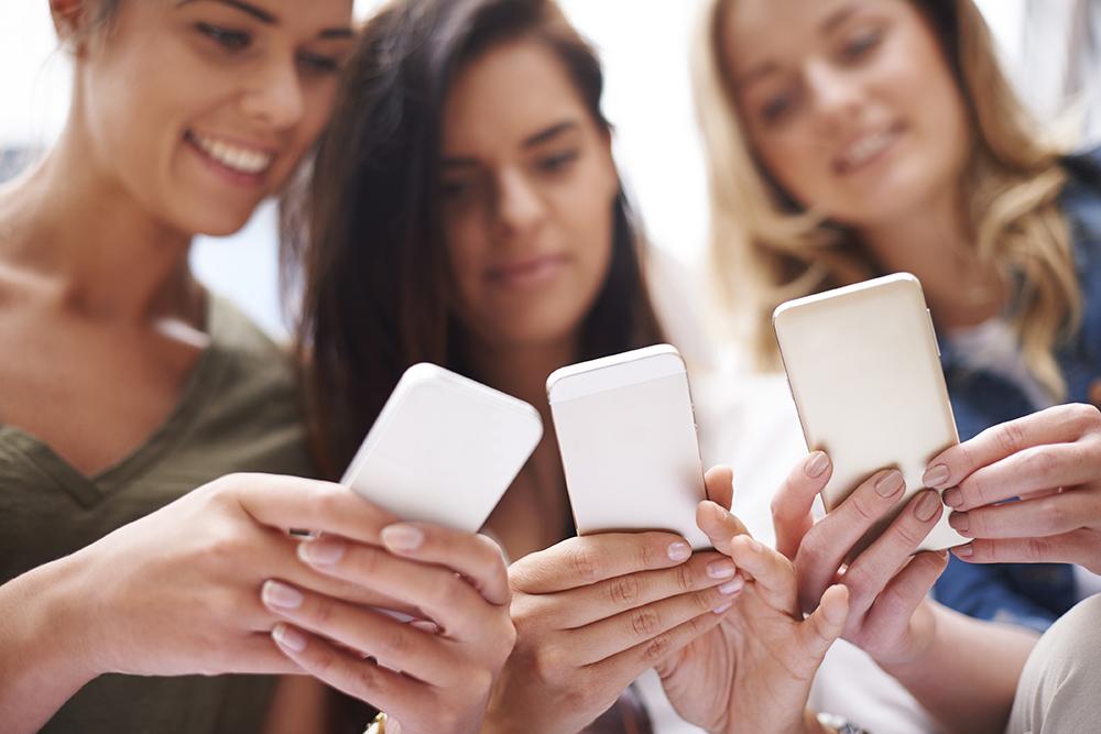 Unge jenter med mobil, digitalt innfødte.