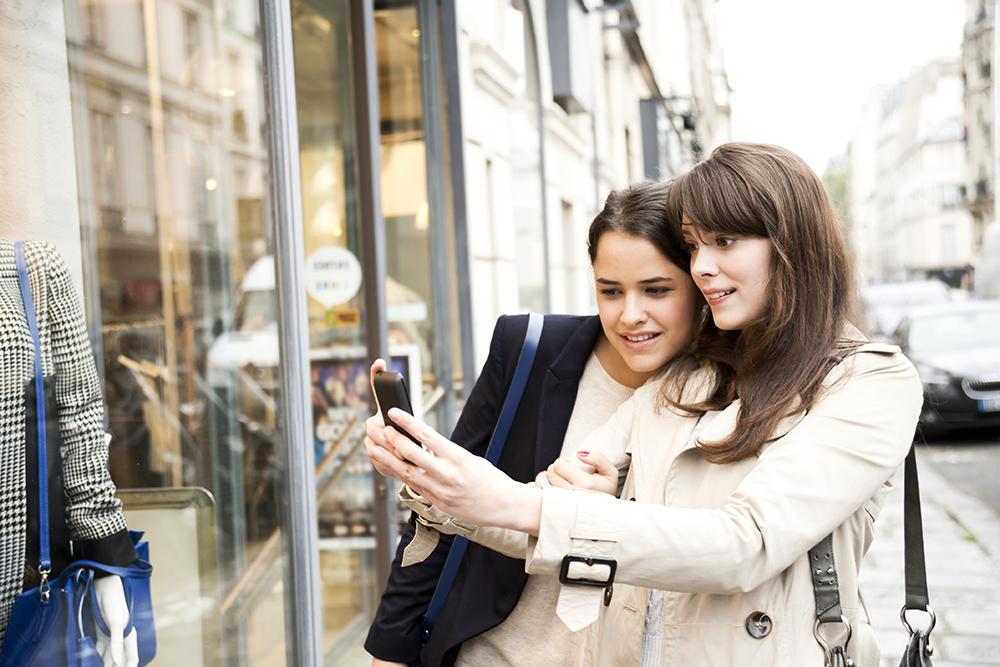To jenter tar bilde av butikken