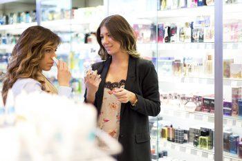 To jenter prøver parfyme i butikken