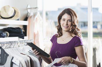 Dame i butikk med nettbrett
