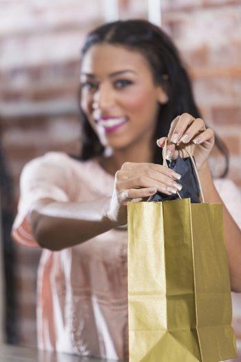 Butikkansatt gir kunde en gave