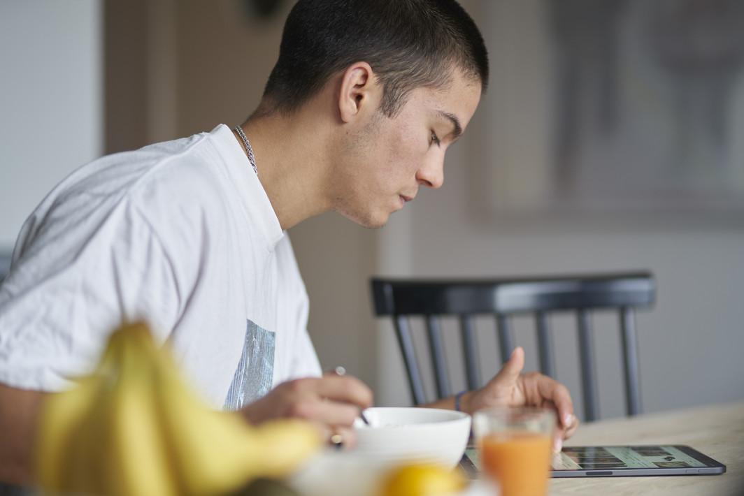 Ung mann surfer på nettbutikk ved frokostbordet