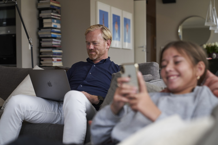 Far og datter i stua, surfer henholdsvis på bærbar og mobil