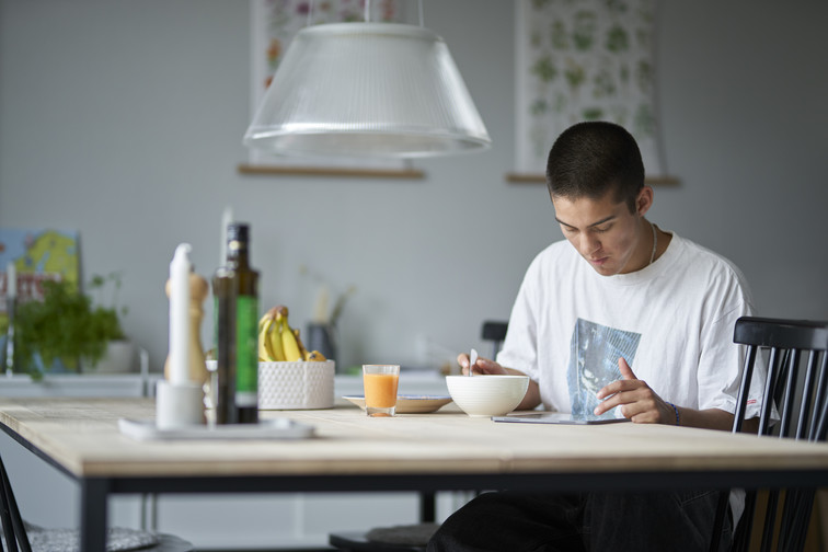 Ung mann ved frokostbordet, nyter mat mens han surfer på lesebrett.