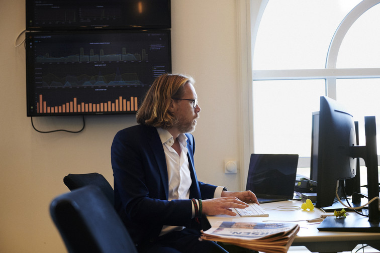 Dresskledd storkar med briller og langt hår, jobber konsentrert på datamaskin.