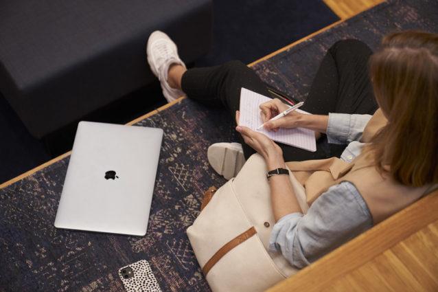Kvinne, sett over skulderen, tar notater på en blokk