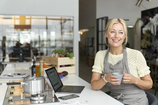 dame med kaffekopp og laptop