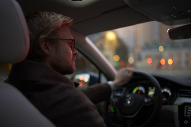 Mann, sett fra baksetet, kjører bil på kveldstid gjennom byen